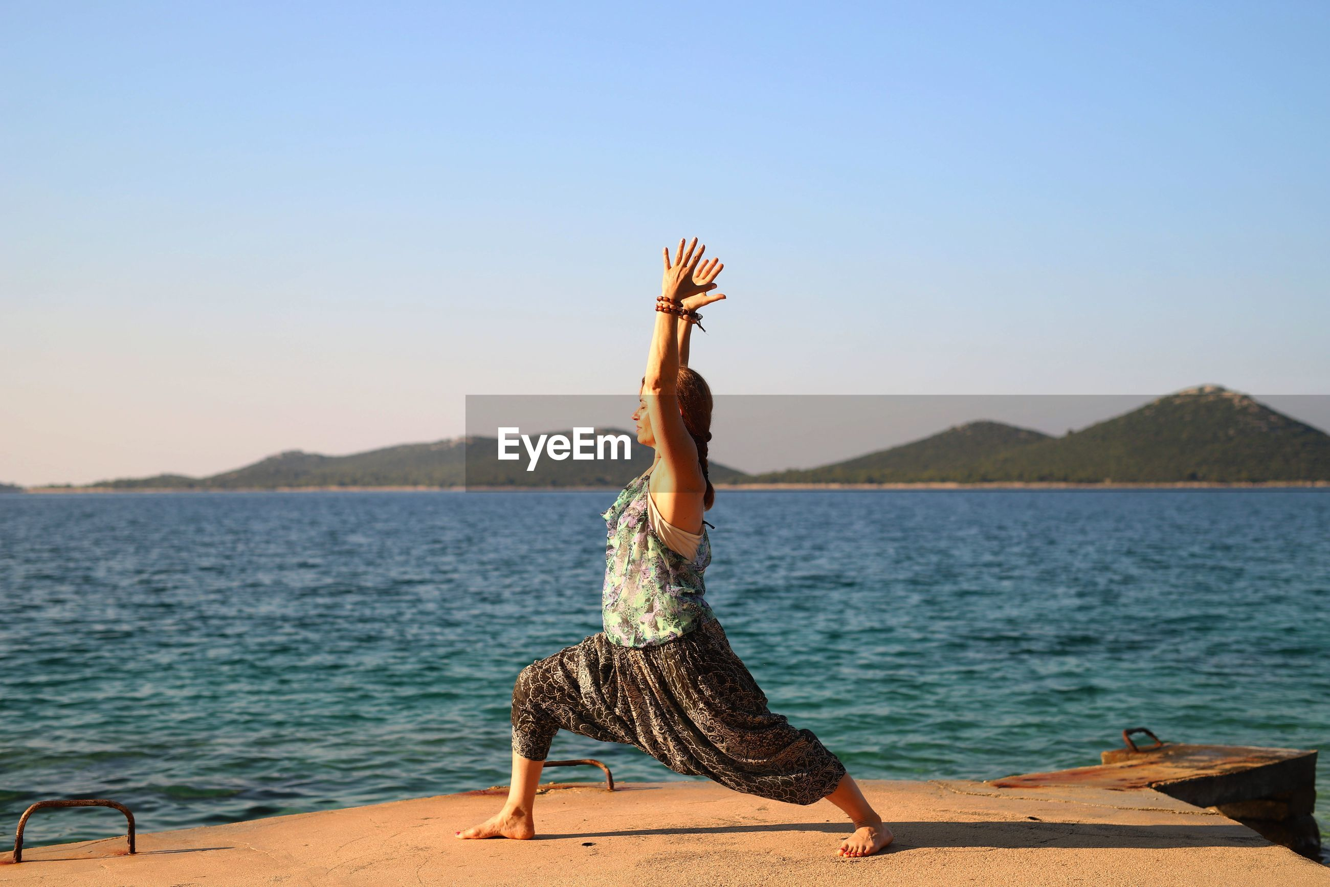 Woman with arms raised doing yoga at beach against clear sky