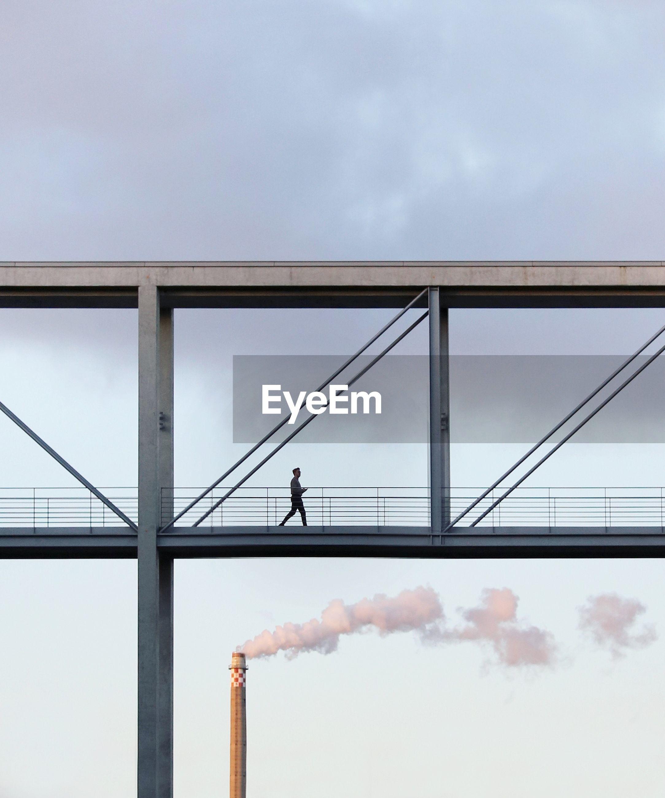 Low angle view of man walking on bridge