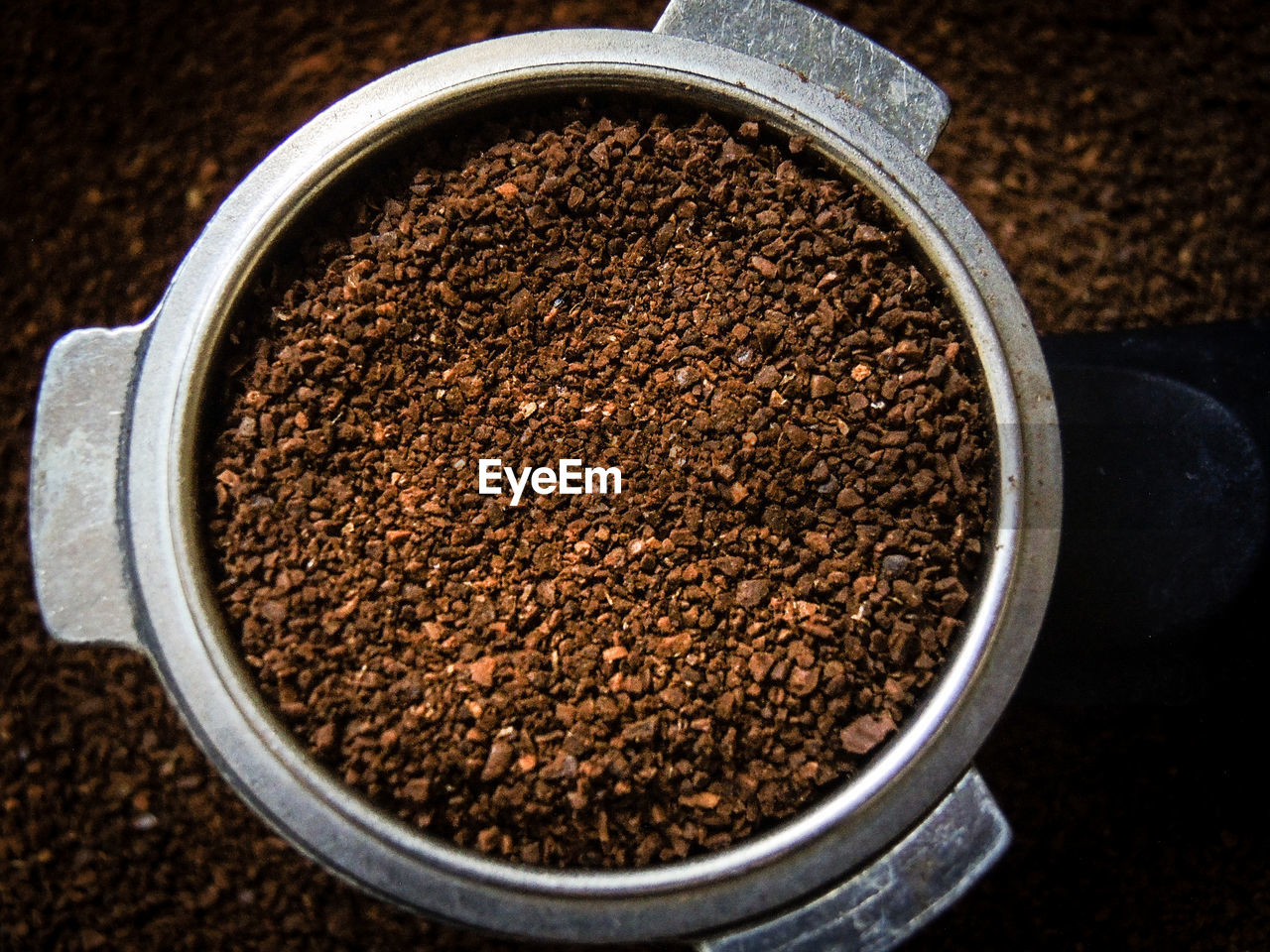 Directly Above Shot Of Crushed Coffee Beans In Container