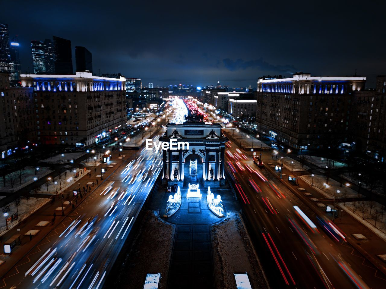 architecture, building exterior, illuminated, built structure, night, city, transportation, high angle view, road, sky, long exposure, building, motion, street, city life, mode of transportation, blurred motion, cityscape, outdoors, land vehicle, no people, light