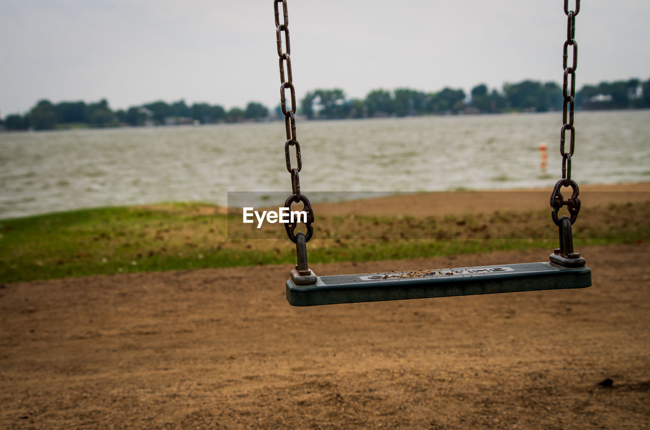 playground, swing, chain, focus on foreground, no people, metal, outdoors, hanging, absence, day, land, nature, water, sand, empty, park, outdoor play equipment, park - man made space