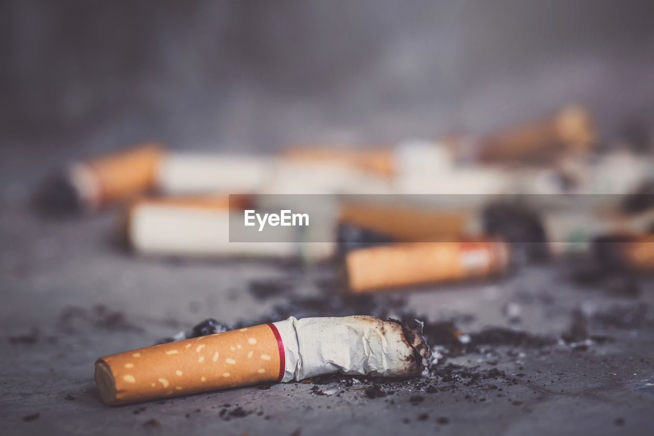 cigarette, sign, smoking issues, selective focus, warning sign, cigarette butt, close-up, social issues, bad habit, no people, risk, focus on foreground, communication, day, burnt, still life, outdoors, city