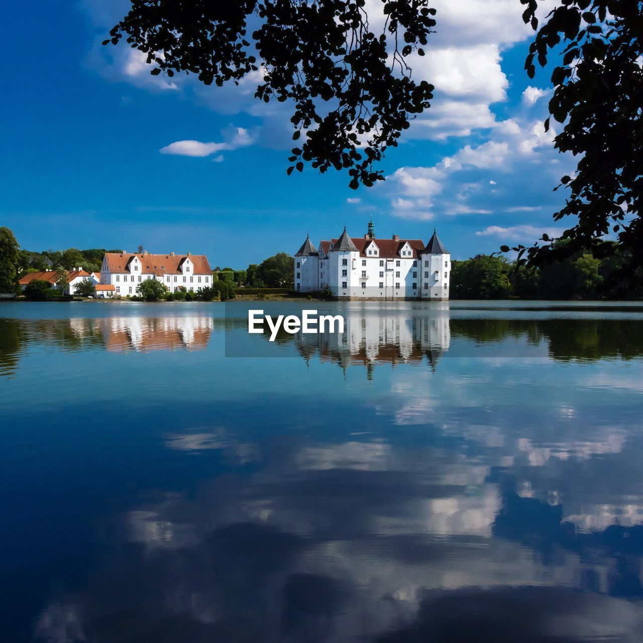 architecture, built structure, building exterior, water, sky, reflection, cloud - sky, building, tree, nature, lake, plant, day, history, the past, travel destinations, no people, castle, waterfront, outdoors