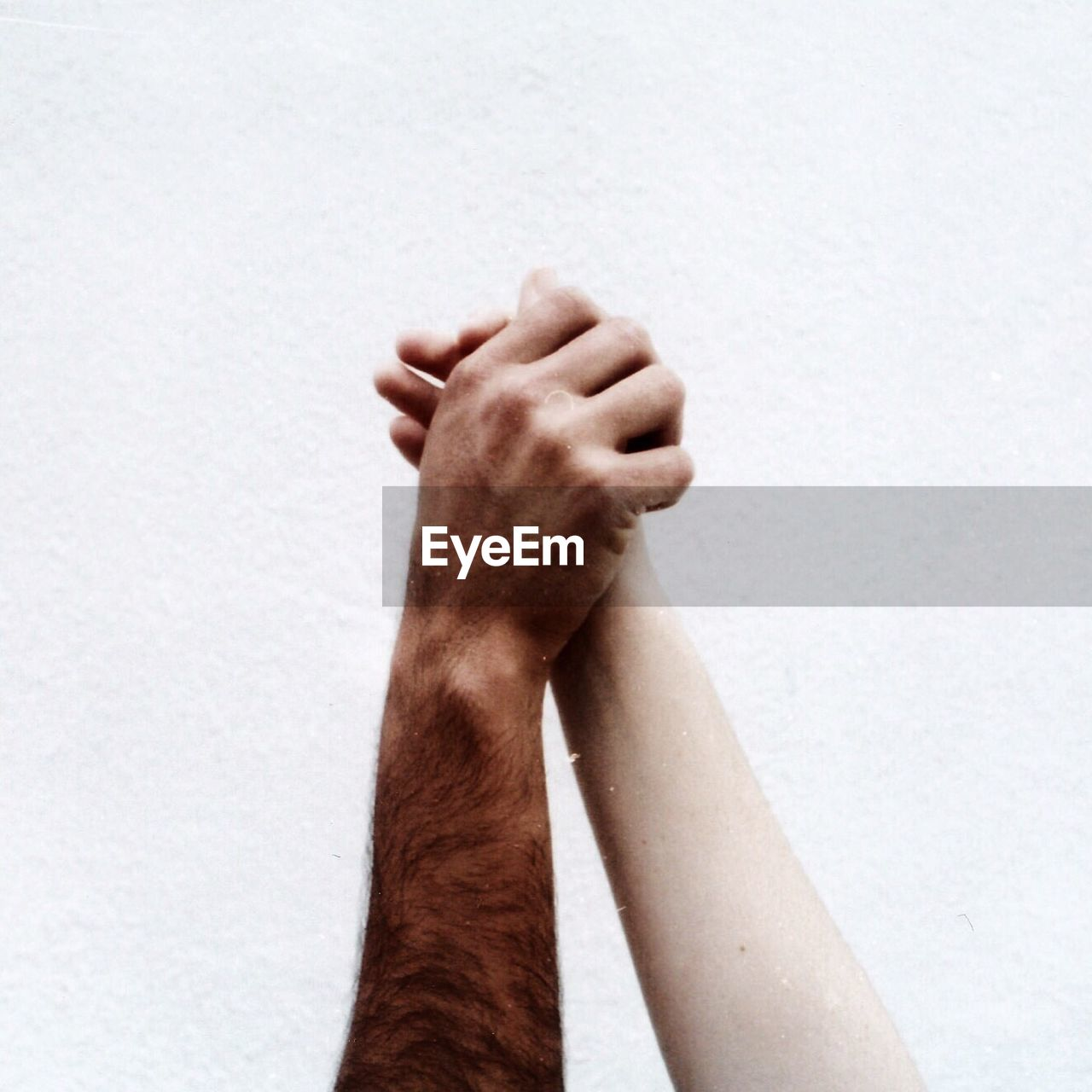 Cropped Image Of People Holding Hands Against White Wall