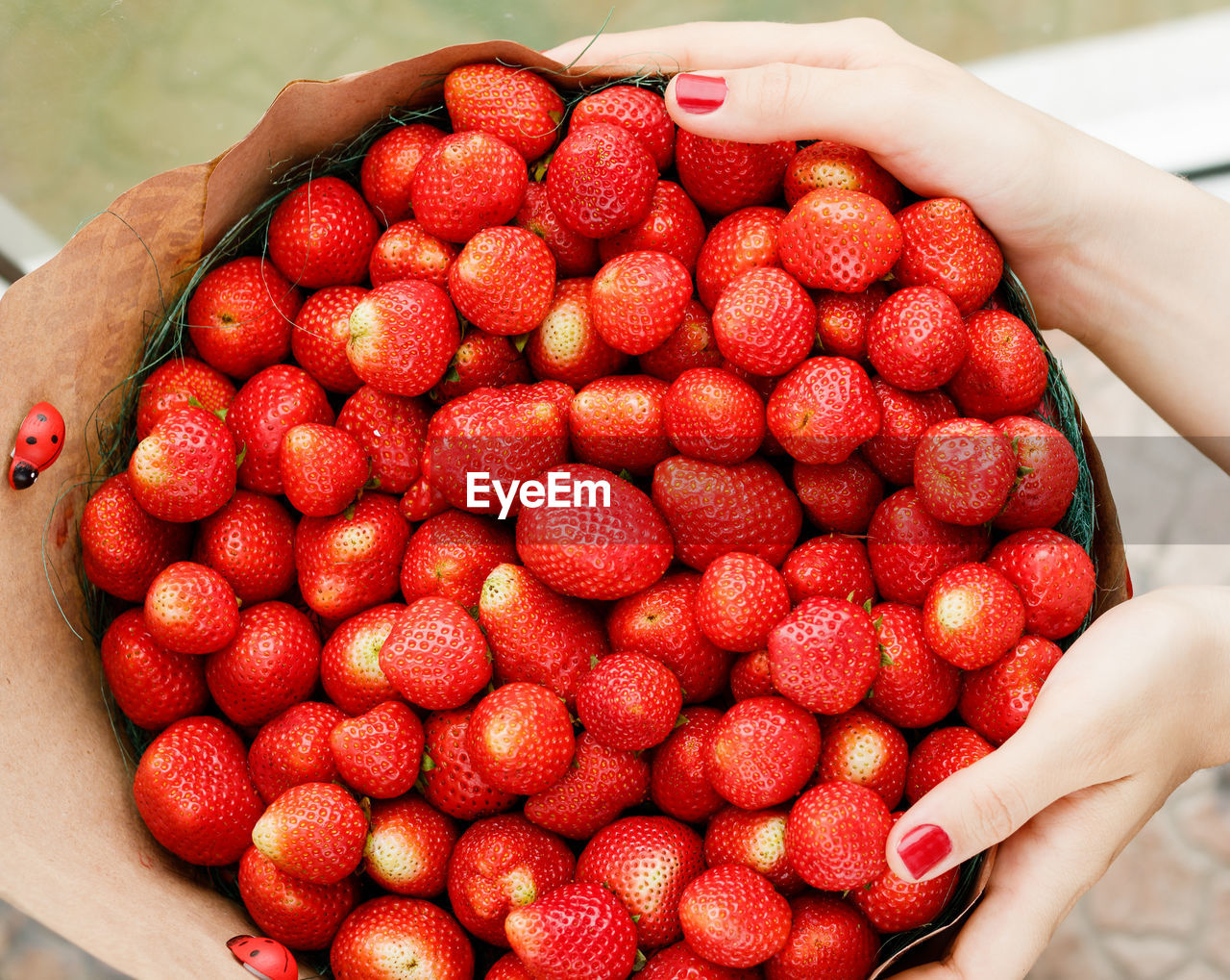 Cropped hands of woman holding strawberries in container
