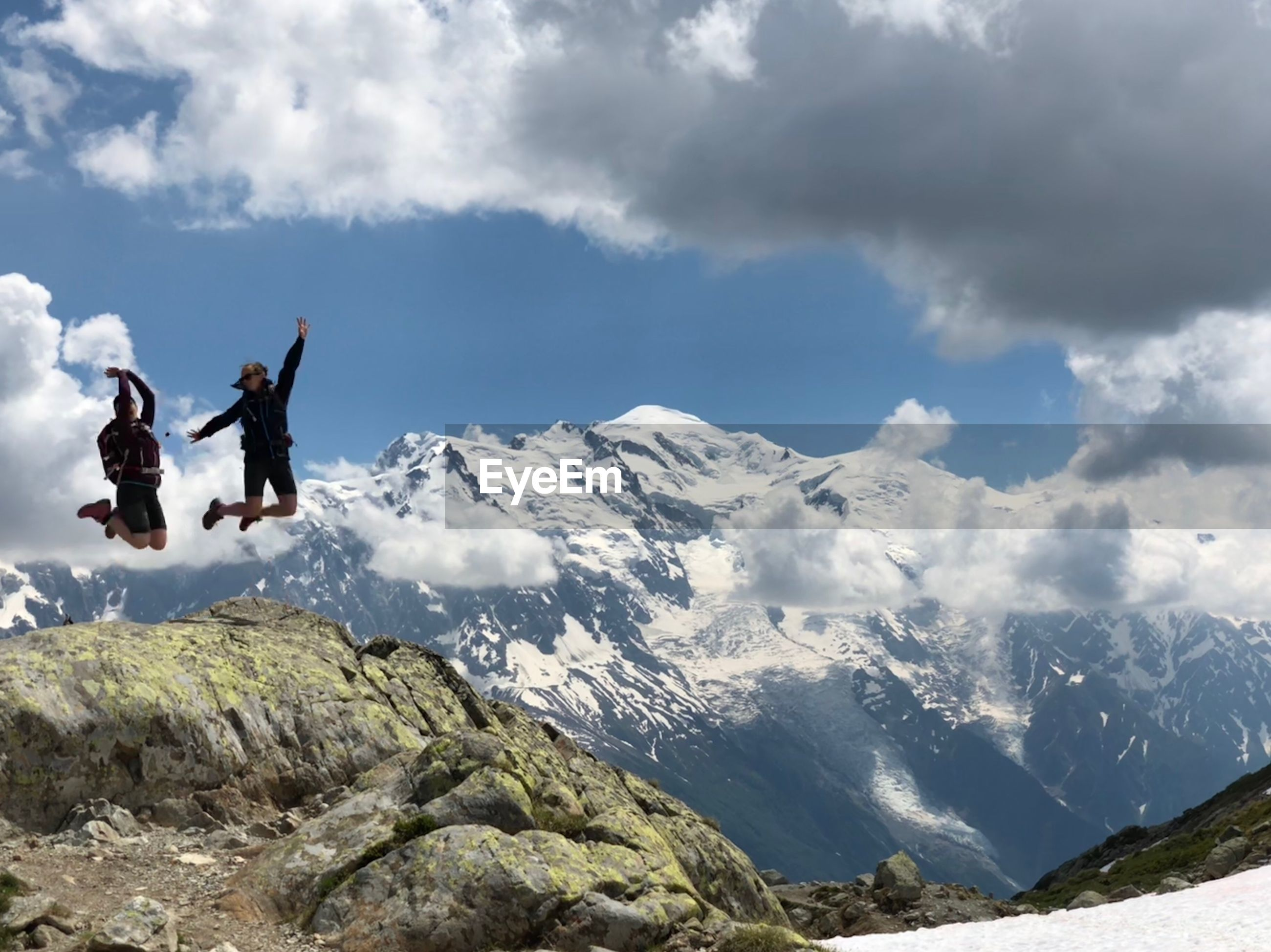 People jumping over mountain during winter