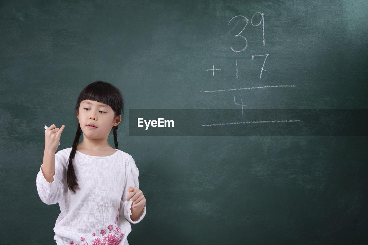 Girl learning mathematics on blackboard