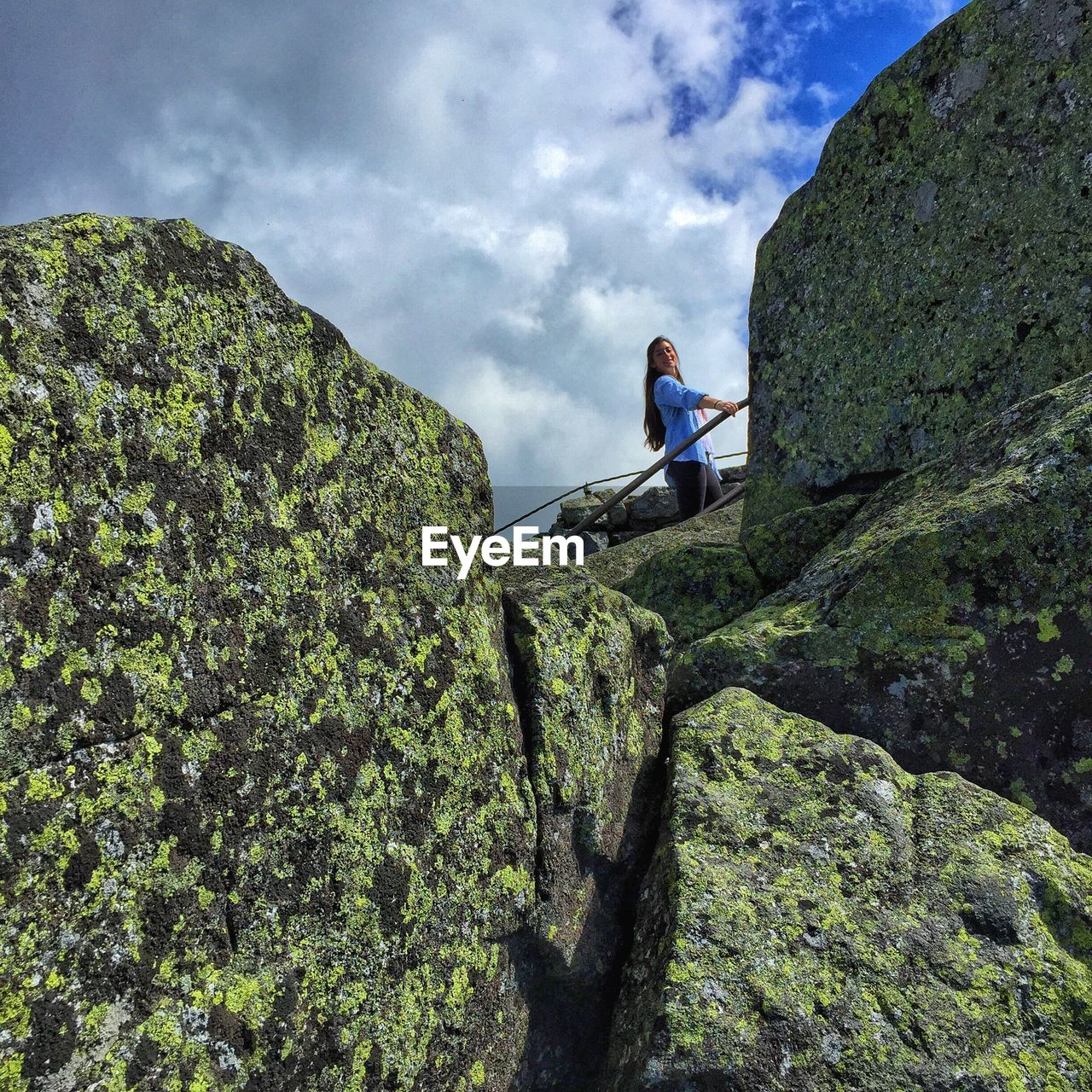 Low angle view of woman on rock against cloudy sky