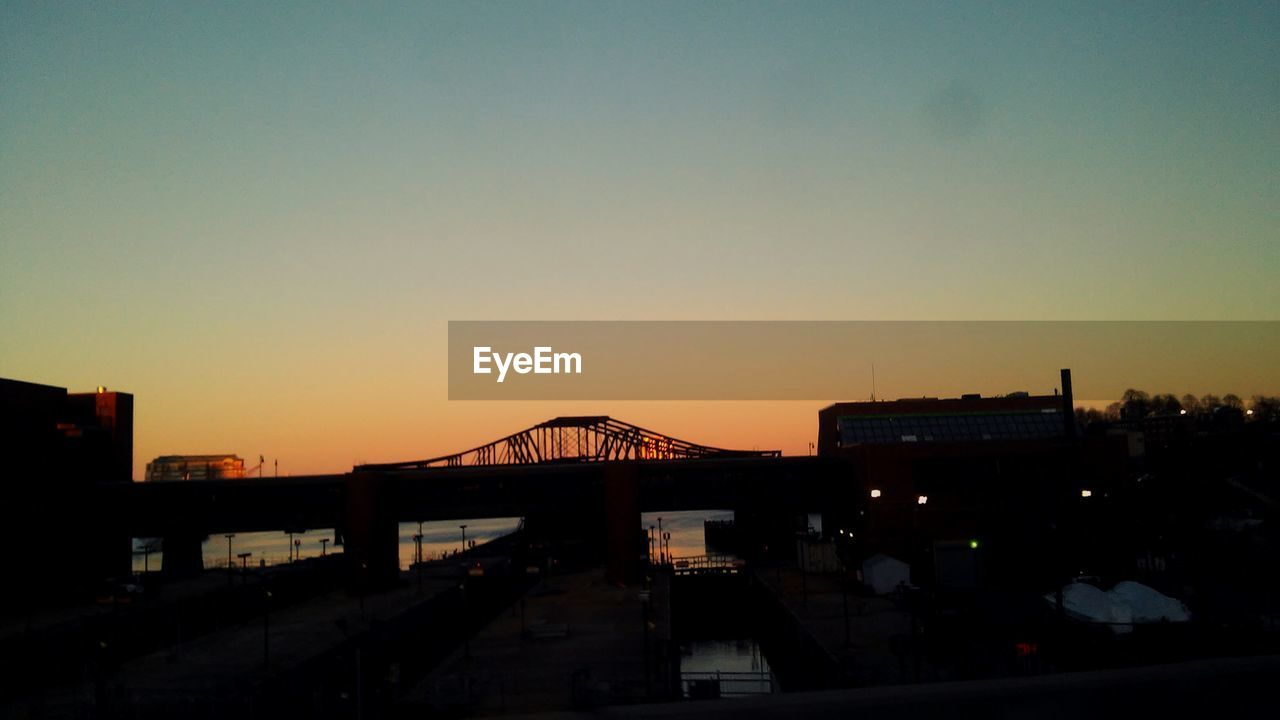 sunset, architecture, built structure, silhouette, building exterior, sky, no people, copy space, city, connection, clear sky, outdoors, bridge - man made structure, transportation, travel destinations, night, cityscape, nature