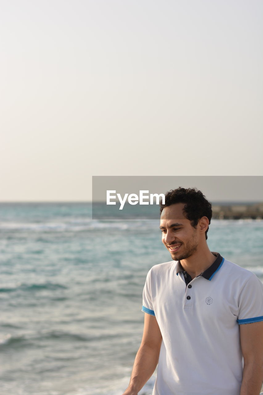 Smiling man standing at beach against clear sky