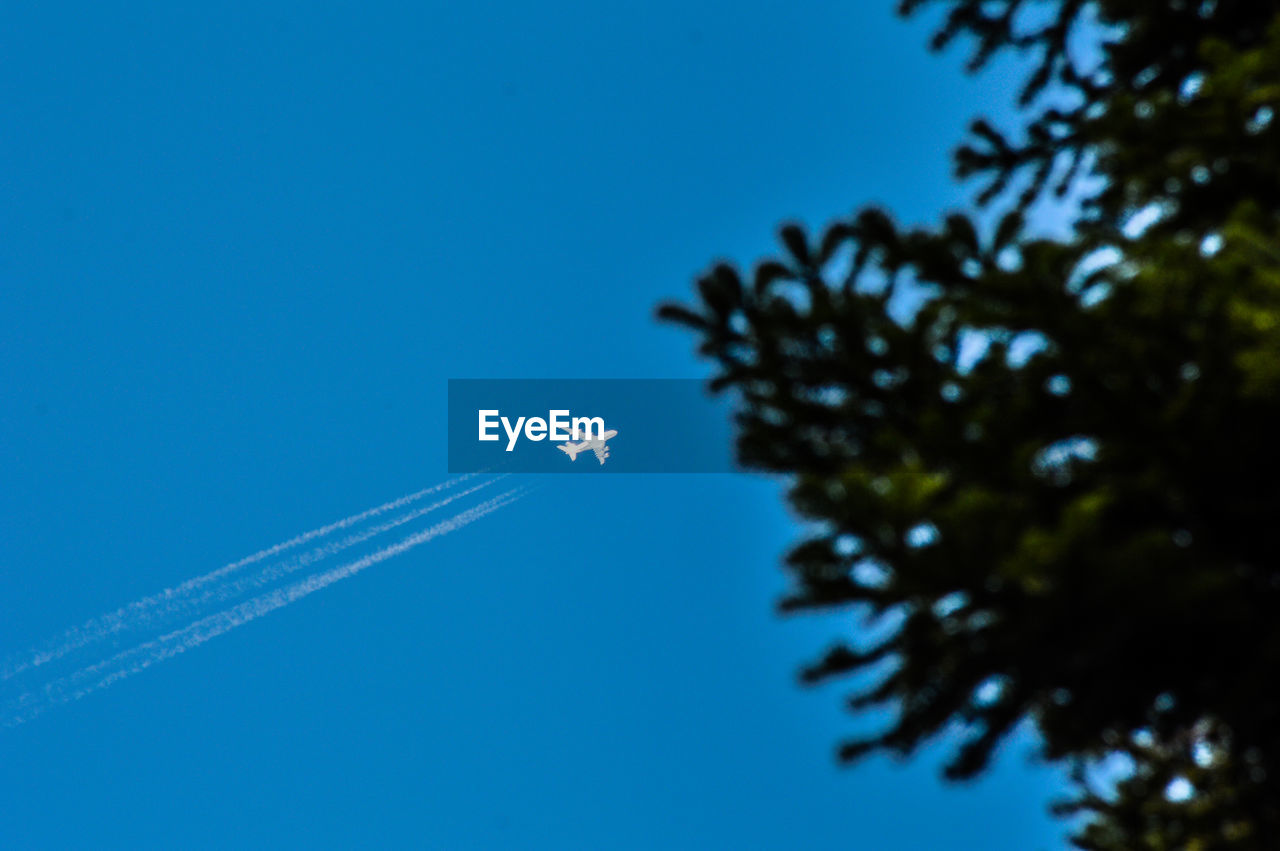 Low Angle View Of Airplane With Vapor Trails Flying Against Clear Sky