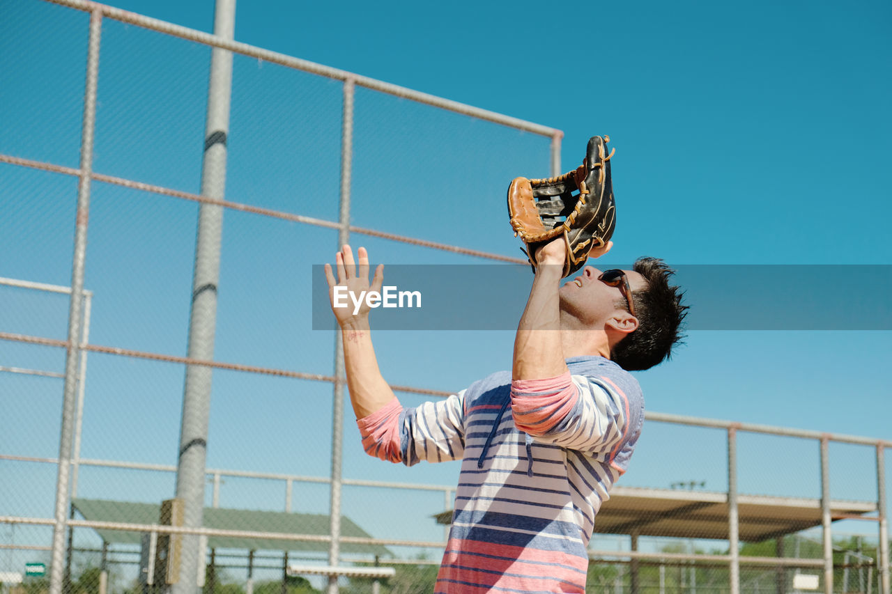 Low angle view of person wearing gloves against sky
