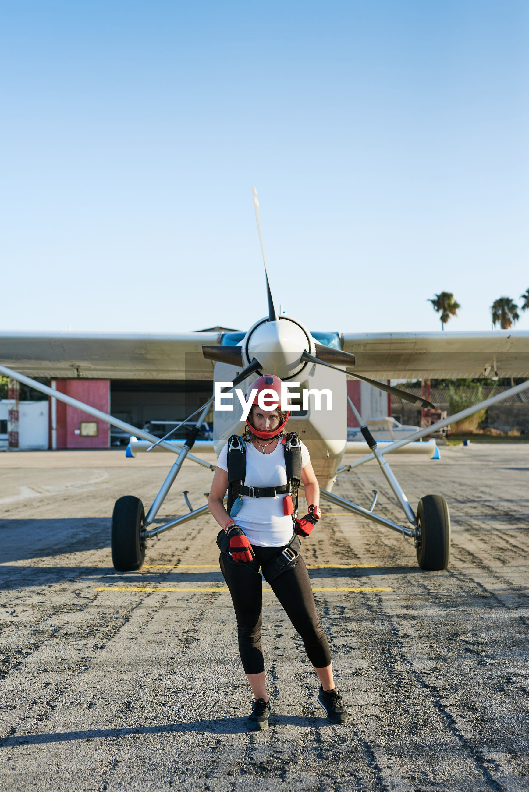 BOY STANDING ON AIRPLANE AGAINST AIRPORT RUNWAY AGAINST CLEAR SKY