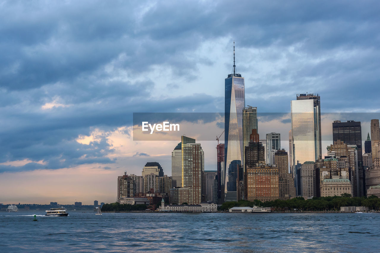 architecture, skyscraper, sky, water, building exterior, cloud - sky, built structure, tower, modern, city, waterfront, travel destinations, cityscape, sea, no people, urban skyline, outdoors, growth, nature, day