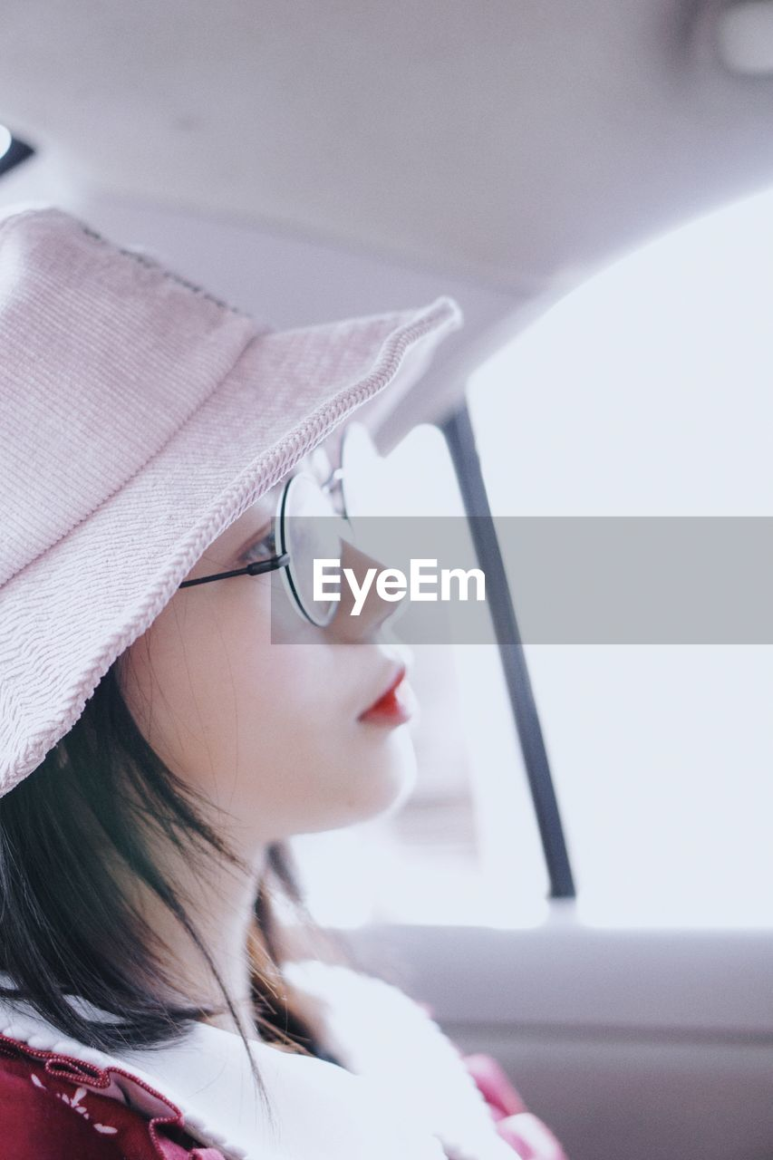one person, real people, headshot, young women, lifestyles, eyeglasses, portrait, glasses, young adult, women, looking, leisure activity, adult, indoors, looking away, vehicle interior, close-up, make-up, mode of transportation, body part, beautiful woman, human face, contemplation