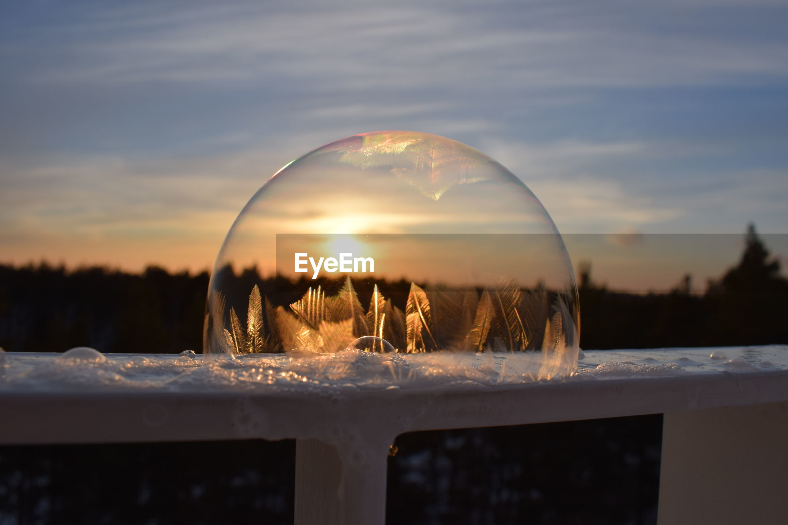 Close-up of bubble on railing against sky during sunset