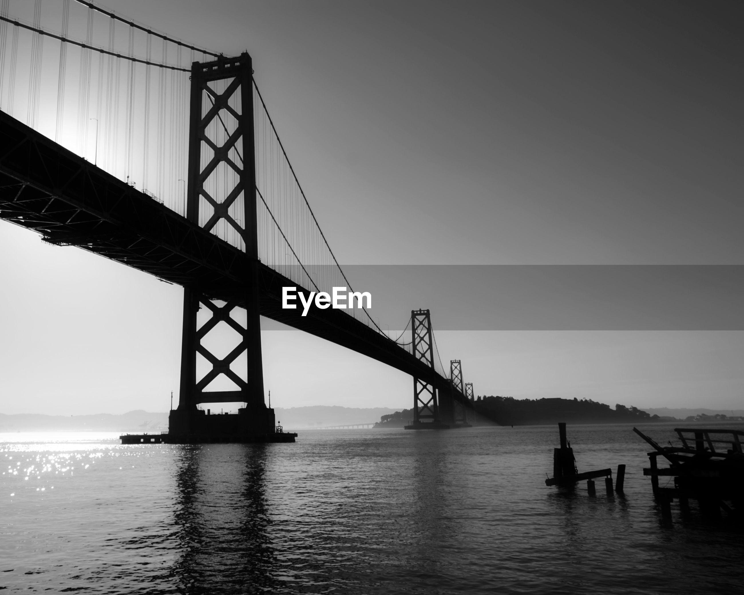 SILHOUETTE OF SUSPENSION BRIDGE IN WATER