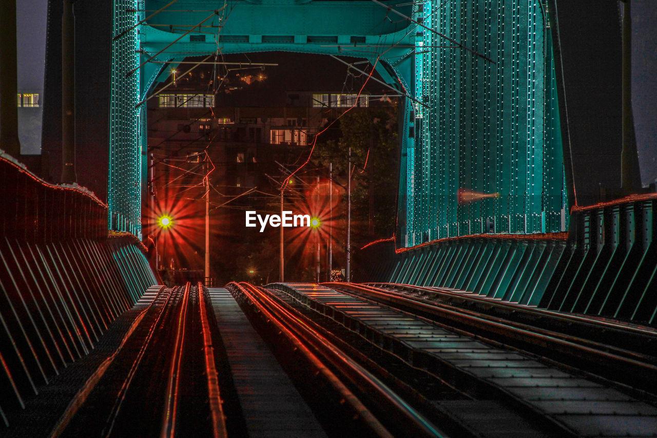 Railroad Tracks In Illuminated City At Night