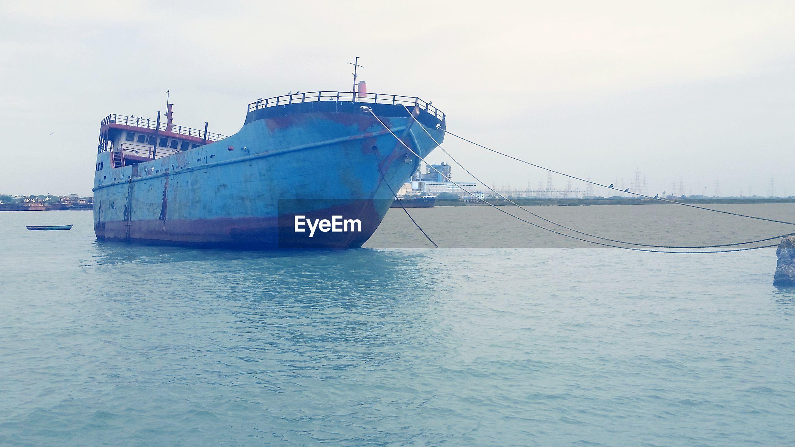 Old ship on sea against sky