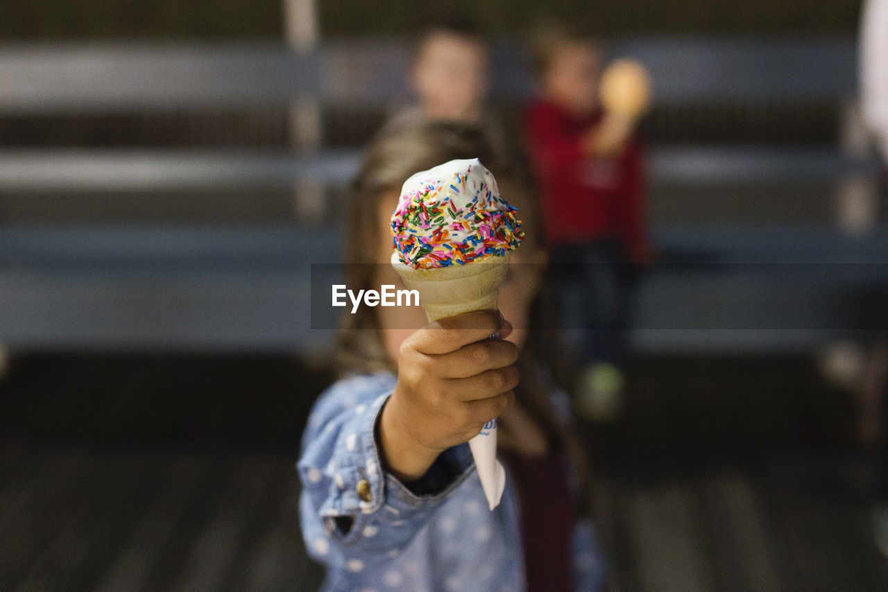 GIRL SHOWING VANILLA ICE CREAM WITH SPRINKLES