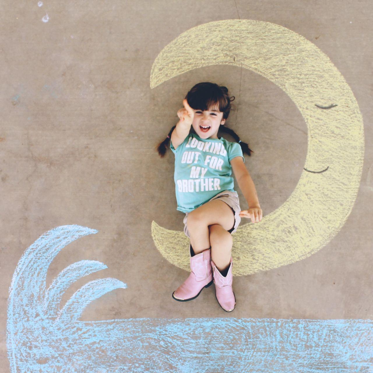 High angle portrait of cute girl lying street