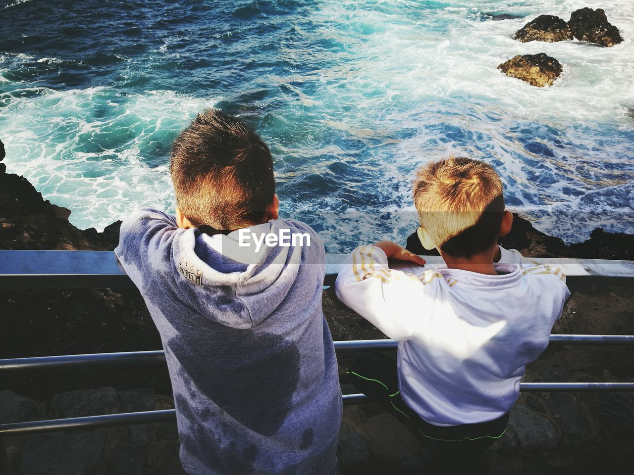 High Angle View Of Boys Leaning On Railing Over Sea