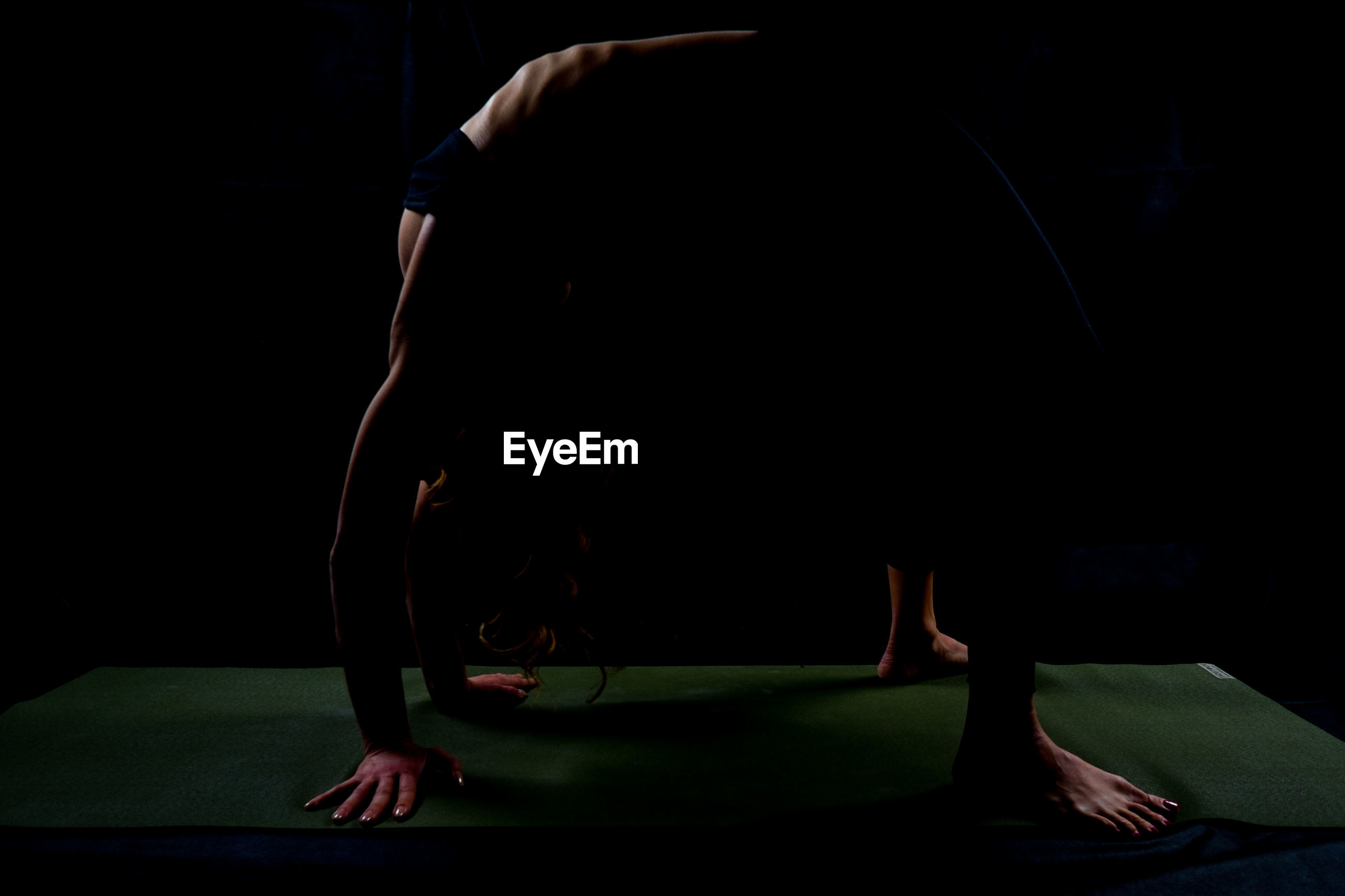 Side view of athlete bending over backwards on exercise mat against black background