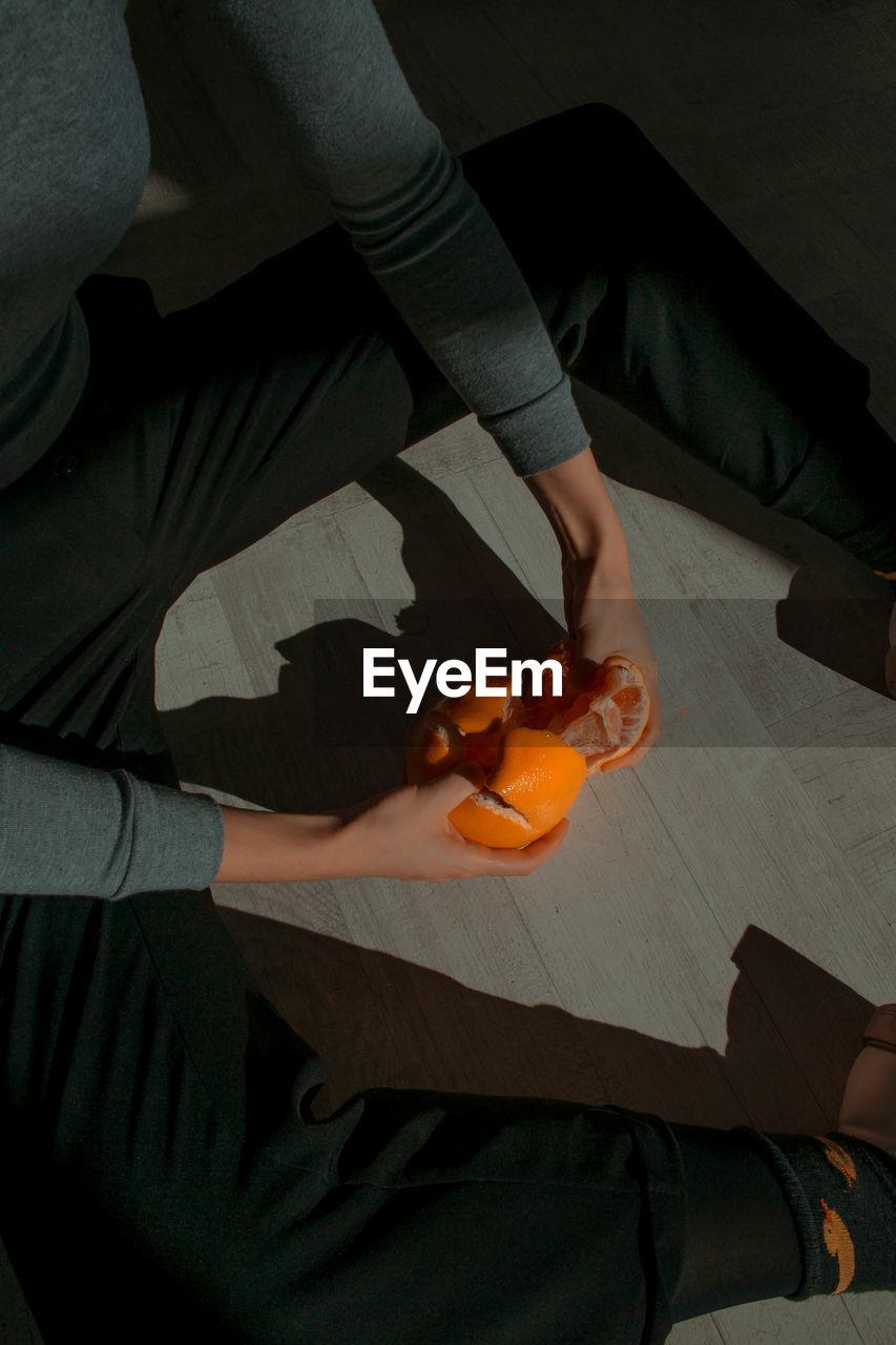 High Angle View Of Cropped Hands Peeling Orange In Darkroom