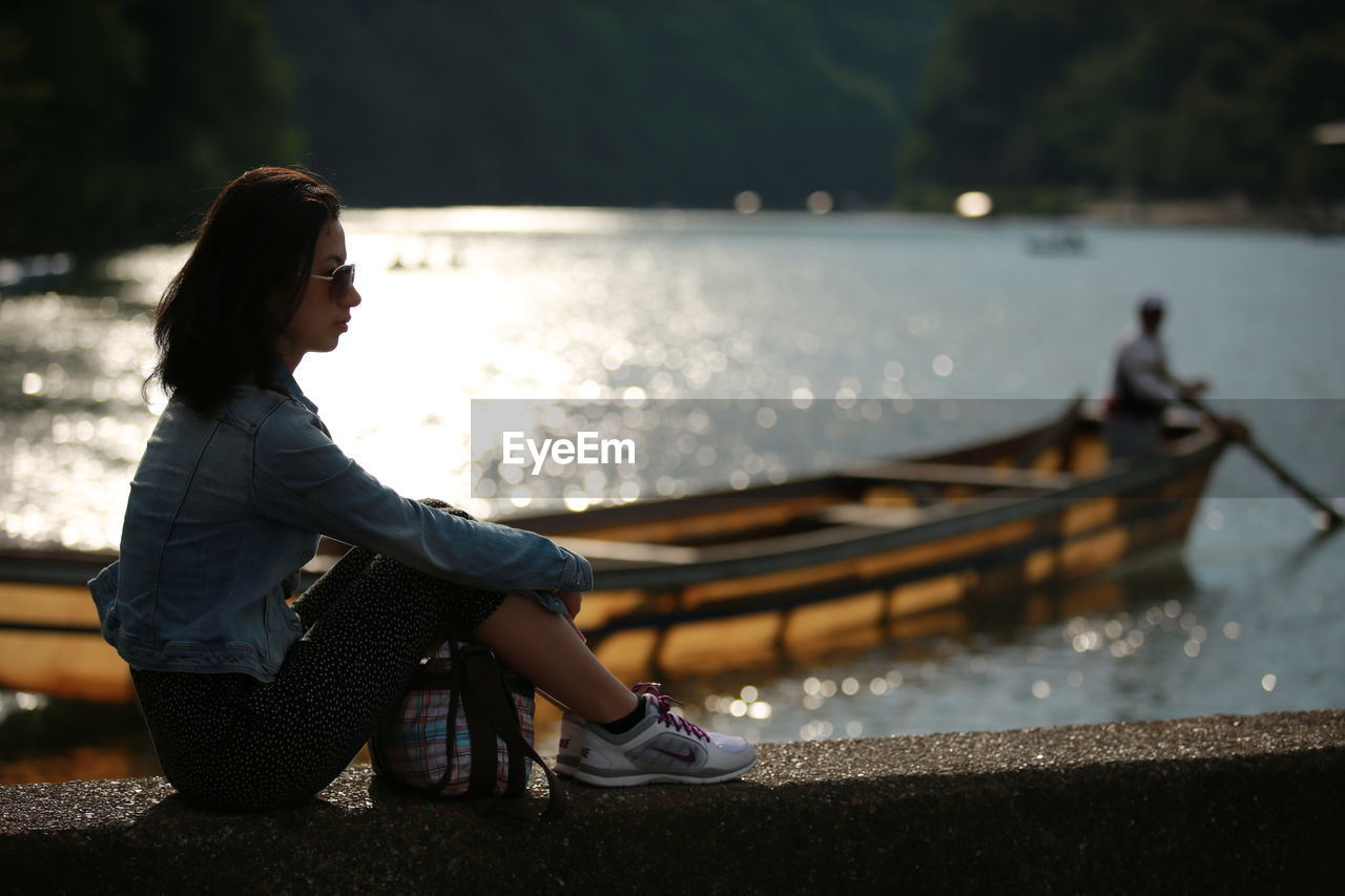 Side View Of Woman Sitting On Retaining Wall Against River
