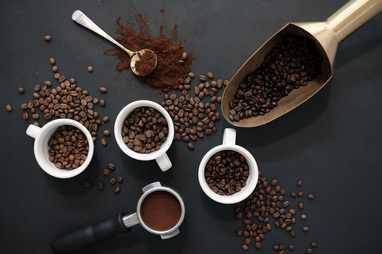 food and drink, coffee - drink, coffee, freshness, food, high angle view, indoors, roasted coffee bean, no people, cup, still life, kitchen utensil, coffee bean, choice, table, eating utensil, spoon, coffee cup, mug, drink