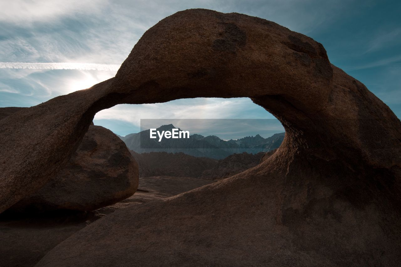 Mountains seen through hole in rock formation against sky