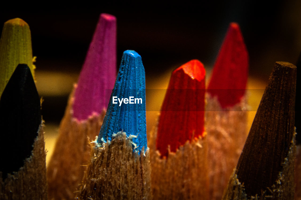 CLOSE-UP OF MULTI COLORED PENCILS IN ROW ON WOOD