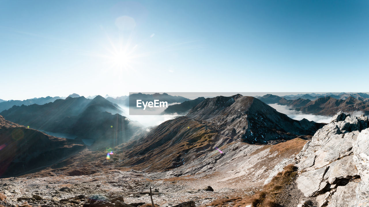 mountain, sky, mountain range, scenics - nature, beauty in nature, sunlight, tranquility, tranquil scene, sun, sunbeam, environment, non-urban scene, landscape, idyllic, lens flare, nature, day, clear sky, remote, sunny, no people, outdoors, bright, mountain peak, formation, snowcapped mountain