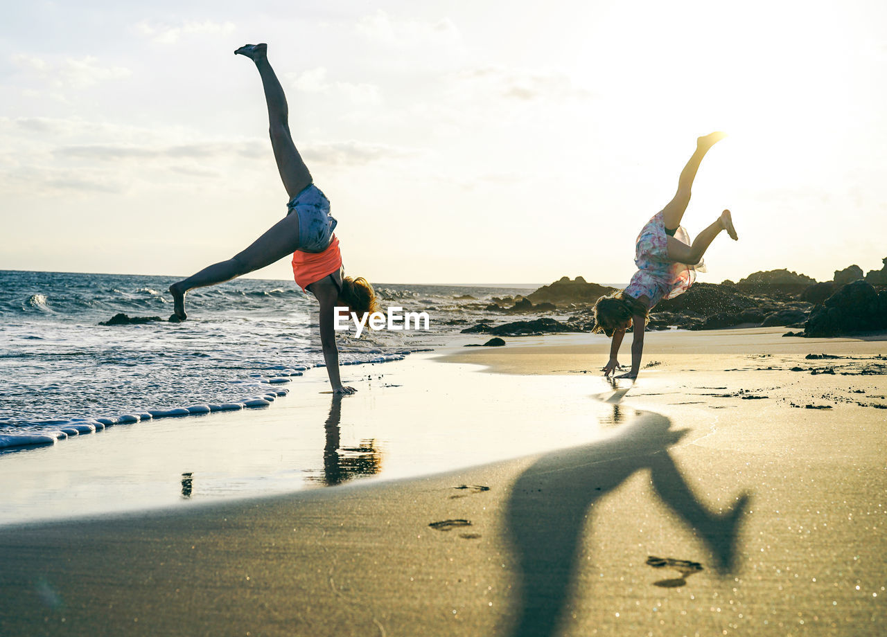 People Doing Handstand At Beach Against Sky