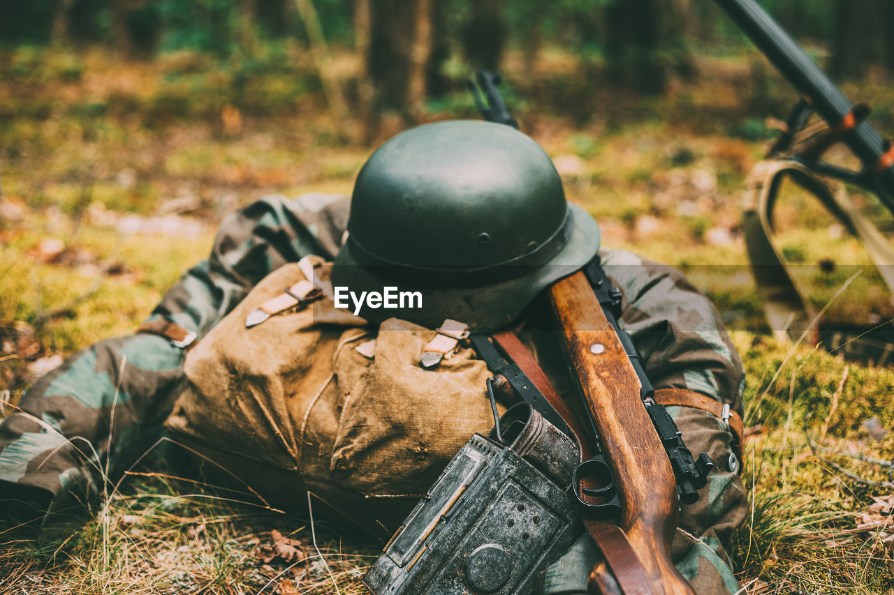 land, field, helmet, nature, day, focus on foreground, metal, grass, weapon, leaf, plant part, autumn, no people, sports equipment, outdoors, plant, high angle view, military, rifle, selective focus
