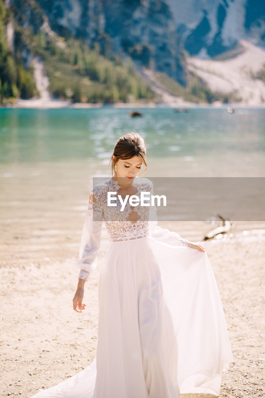 Beautiful bride standing by lakeshore