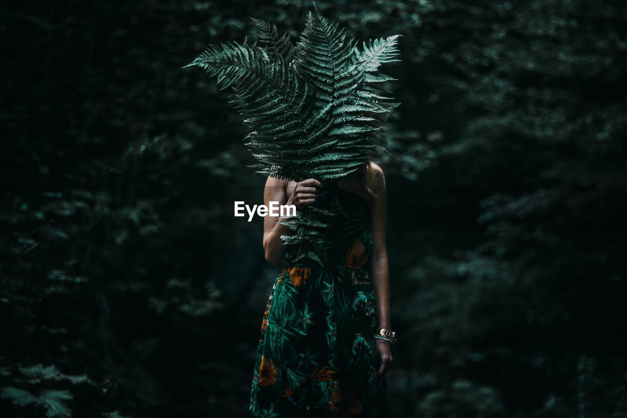 Woman Covering Face With Leaves While Standing In Forest