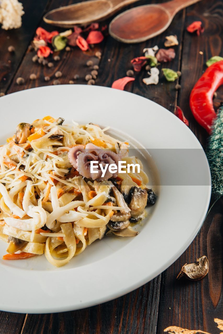 food and drink, food, table, pasta, italian food, freshness, plate, ready-to-eat, healthy eating, serving size, indoors, high angle view, wellbeing, still life, bowl, no people, close-up, kitchen utensil, meal, wood - material, herb, spaghetti, garnish, temptation
