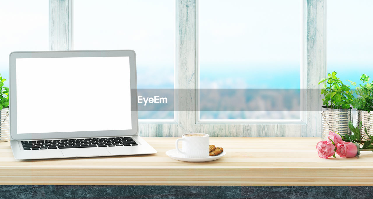Laptop With Food And Drink On Wooden Table By Window
