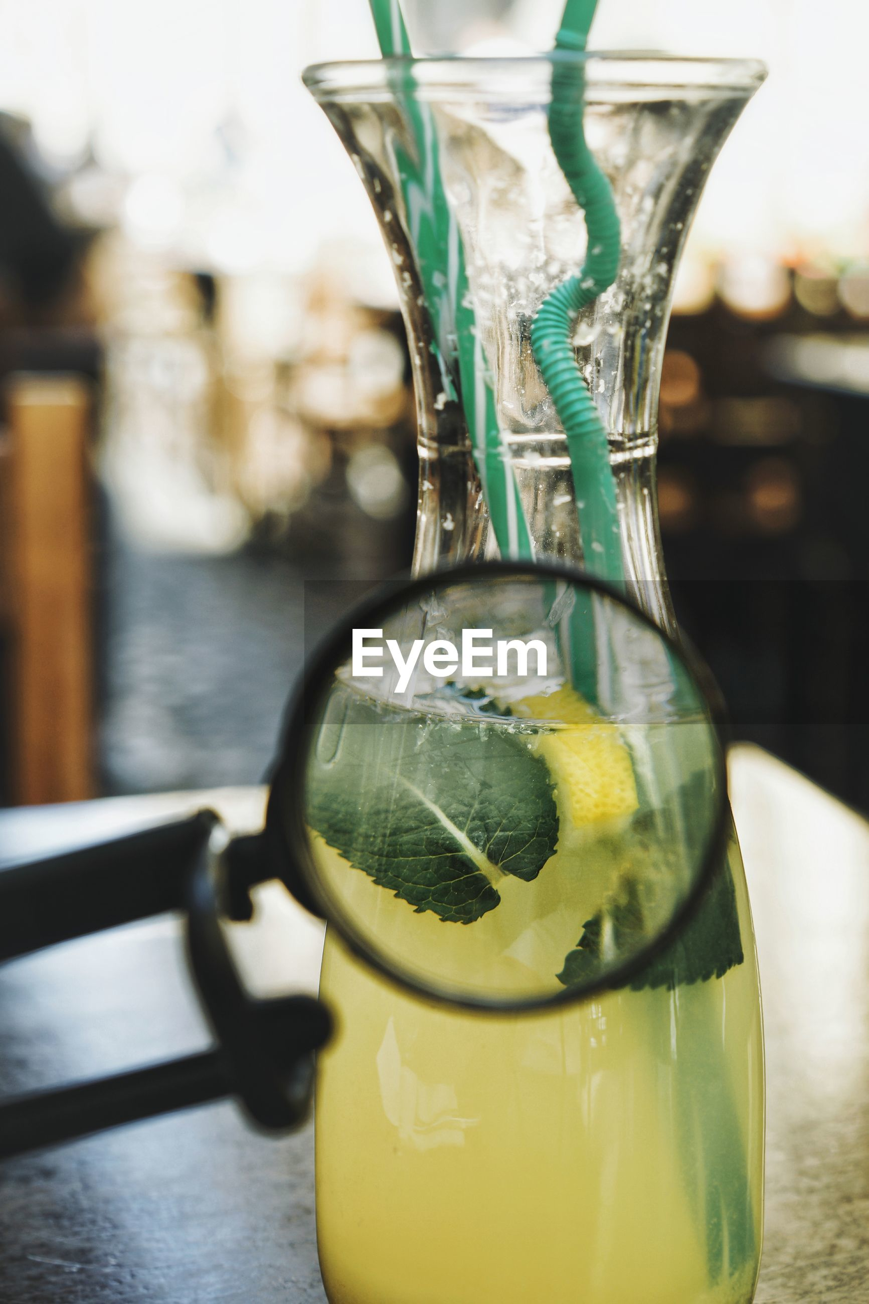 Close-up of magnifying glass against drink on table