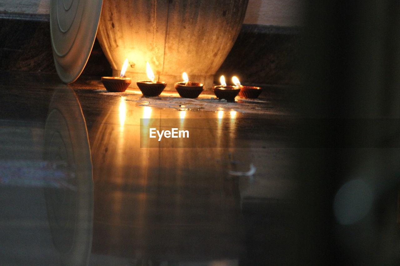 flame, burning, reflection, heat - temperature, candle, no people, indoors, illuminated, spirituality, oil lamp, diya - oil lamp, close-up, day