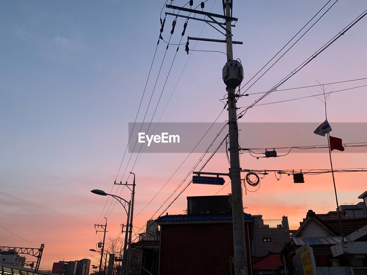 sky, architecture, sunset, built structure, building exterior, low angle view, cable, technology, connection, power line, nature, building, electricity, communication, no people, silhouette, city, electricity pylon, power supply, orange color, outdoors