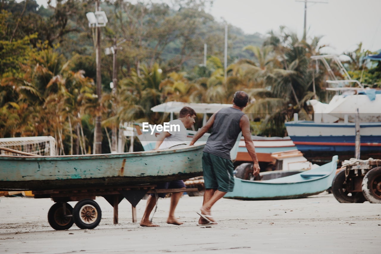 real people, transportation, mode of transportation, men, day, full length, nature, nautical vessel, two people, people, water, young adult, tree, outdoors, plant, focus on foreground, adult, lifestyles, standing, togetherness