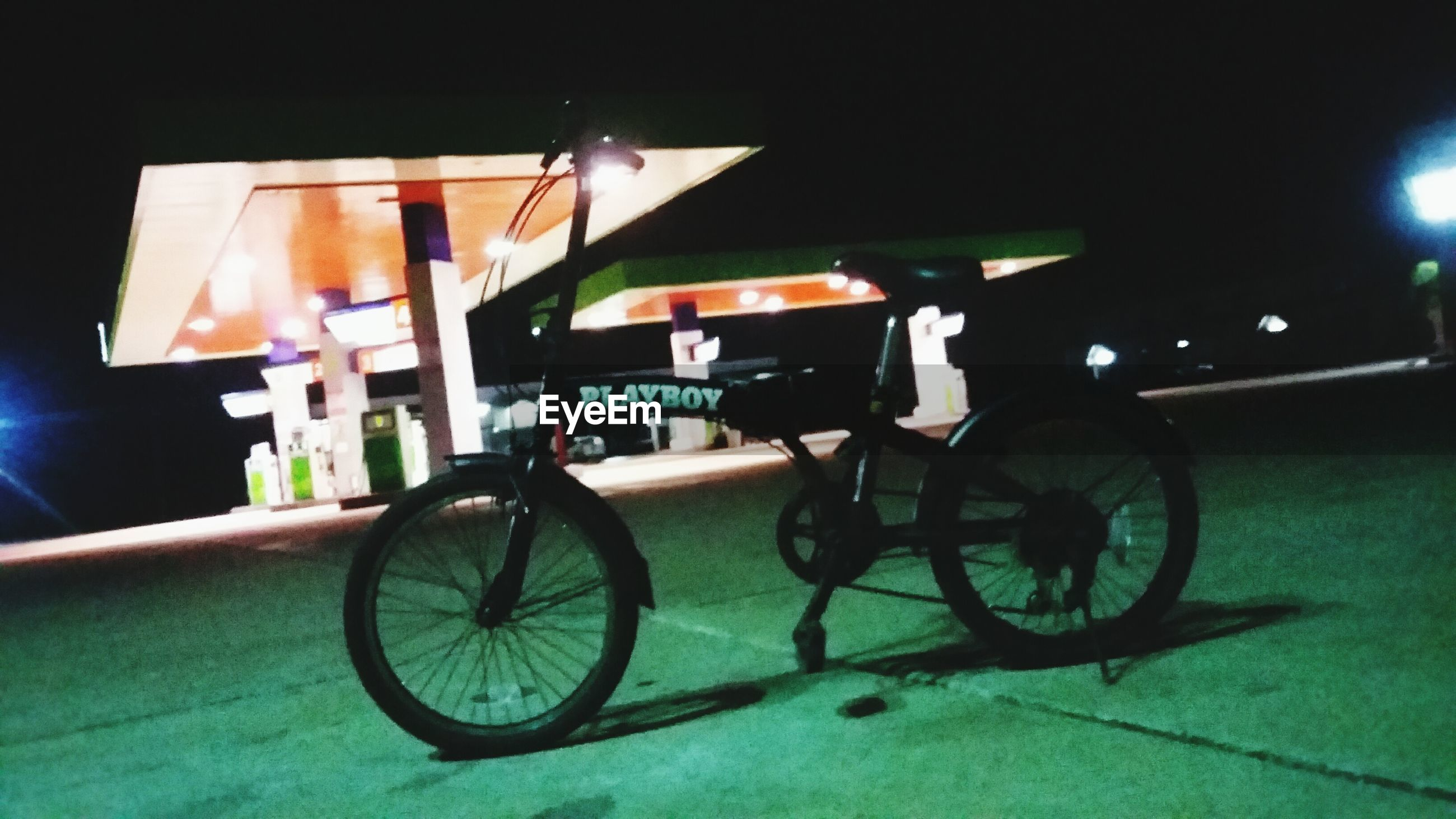 transportation, mode of transport, land vehicle, bicycle, stationary, parking, parked, car, street, night, travel, motorcycle, road, no people, parking lot, sunlight, illuminated, outdoors, wheel, side view