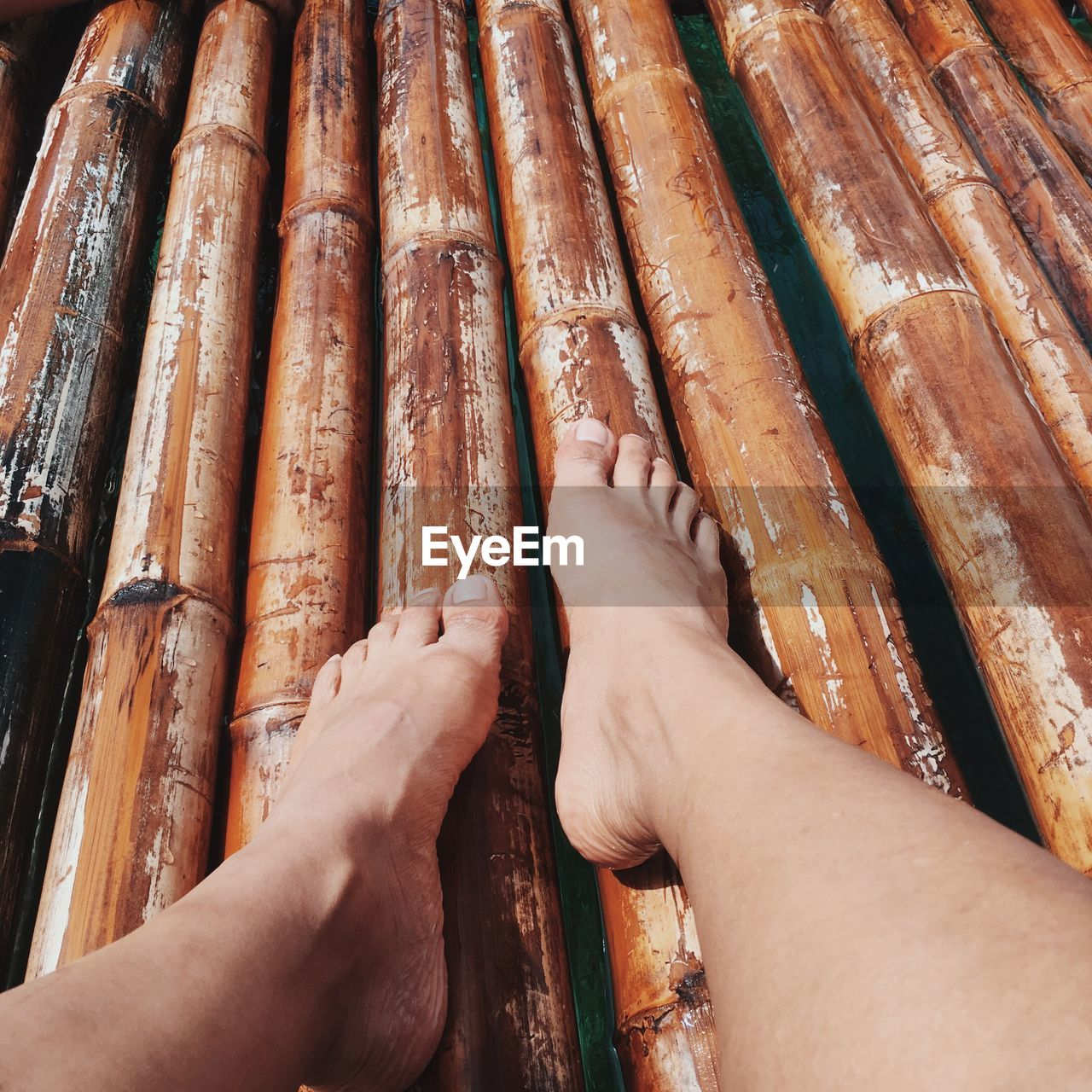 Low section of person sitting on wooden raft