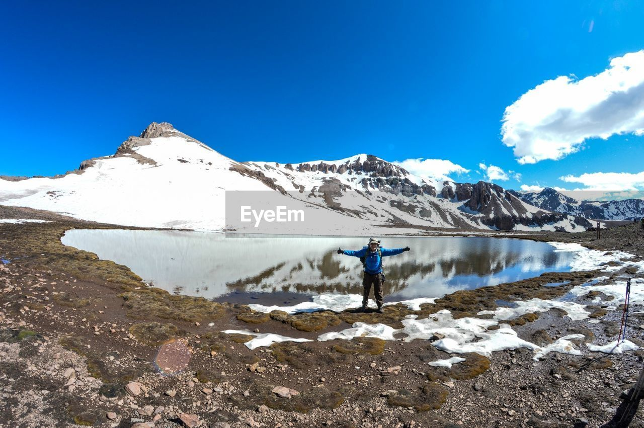 sky, mountain, beauty in nature, scenics - nature, nature, blue, tranquil scene, tranquility, leisure activity, day, one person, real people, mountain range, lifestyles, snow, water, winter, cold temperature, cloud - sky, non-urban scene, snowcapped mountain, outdoors
