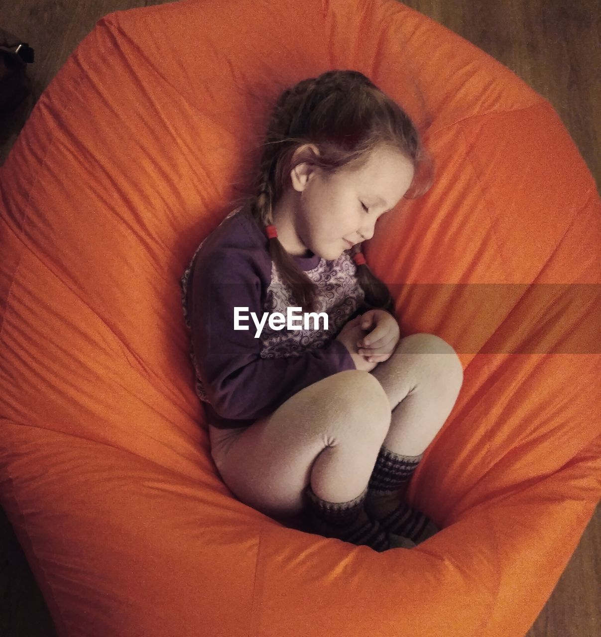 High Angle View Of Girl Sleeping On Orange Bean Bag At Home