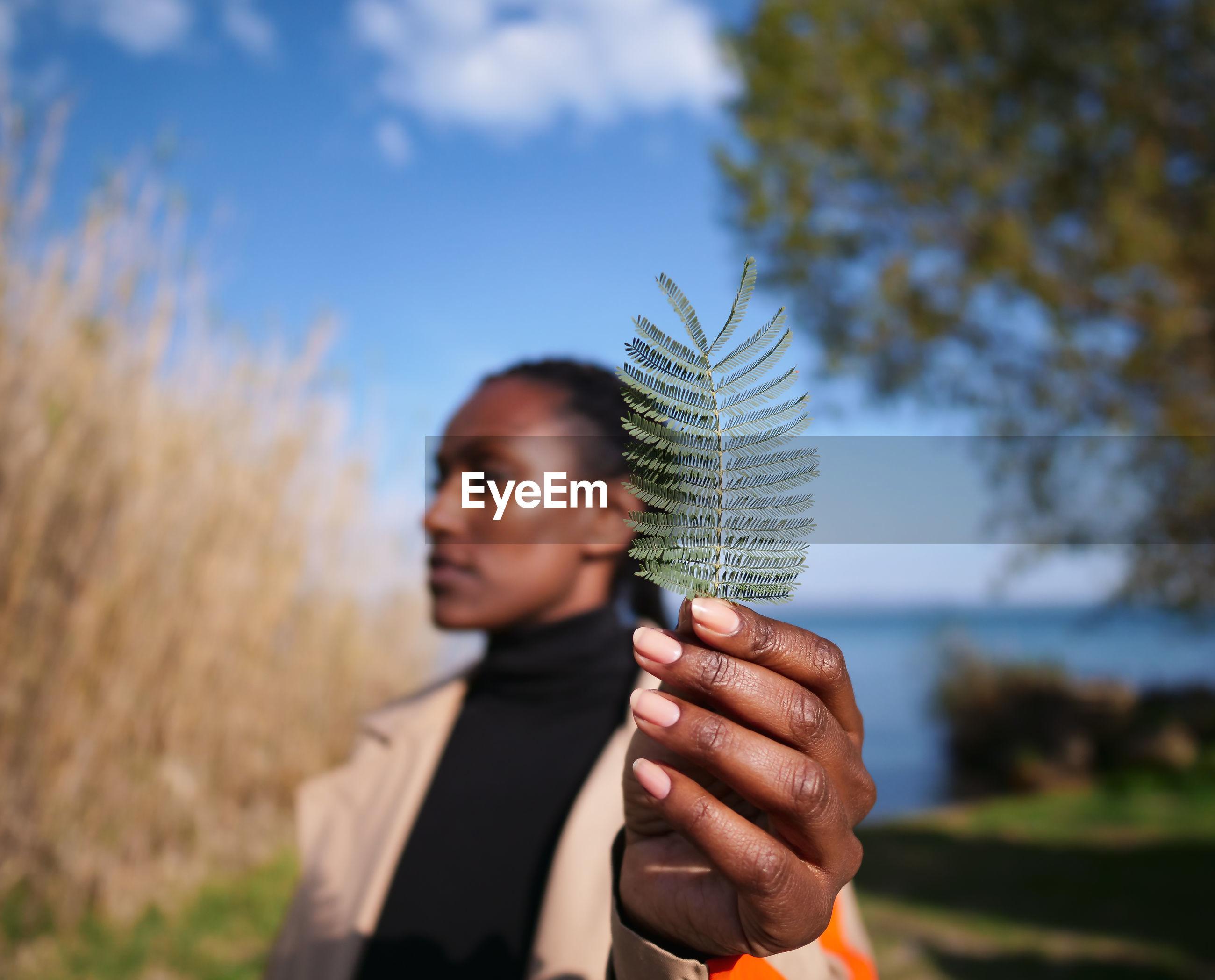 Woman holding fern against sky