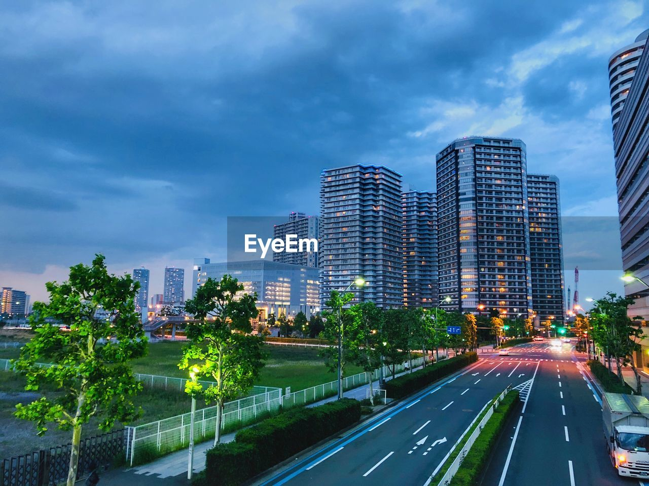 city, architecture, sky, built structure, building exterior, cloud - sky, transportation, building, road, nature, plant, tree, office building exterior, modern, no people, city life, illuminated, skyscraper, cityscape, sign, outdoors