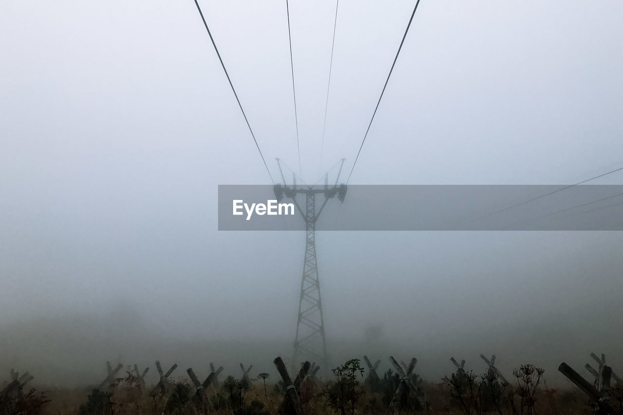cable, power line, electricity, connection, electricity pylon, power supply, fuel and power generation, day, low angle view, no people, tree, outdoors, field, nature, technology, fog, landscape, sky